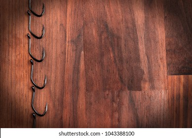 Fishing hooks isolated on a wooden background. Ornament from hooks.
