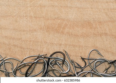 Fishing hooks on wooden background. Top view.