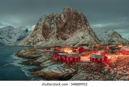 Fishing hut (rorbu) in the Hamnoy and Lilandstinden mountain peak at sunset - Reine, Lofoten islands, Norway