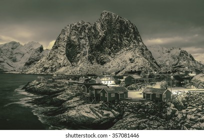Fishing hut (rorbu) in the Hamnoy and Lilandstinden mountain peak at sunset - Reine, Lofoten islands, Norway (stylized retro)