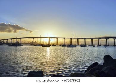 Fishing and leisure boats under the beautiful sunrise over the Coronado Bridge, San Diego California