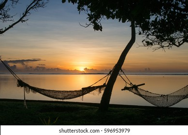 Fishing net hammocks hung from trees at sunset at Coconut Point