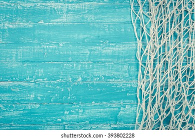 Fishing net from right side of old turquoise painted board background with copy space.