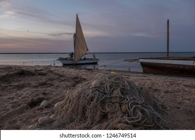 fishing net with traditional ail boats in background
