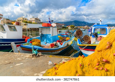 Fishing nets in foreground with Greek boats in port,in background Samos island, Greece