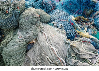 Fishing nets pattern mess stacked at port.
