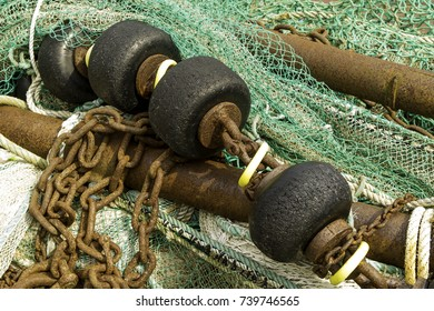 Fishing nets with rusty iron poles, ropes and black net floats.