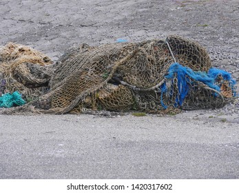 Fishing nets stored on gray concrete floor. Large loops with strong ropes, waiting for use aboard a fishing boat