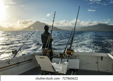 Fishing in the ocean. Saltwater fishing. Deep sea. Man standing on a boat with fishing rod