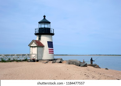 Fishing off the sandy beach by Brant Point lighthouse on Nantucket Island in Masssachusetts. The beacon is wrapped in an American flag to welcome visitors to the island.
