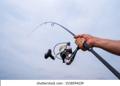 Fishing on the lake. Male hand holding a fishing rod and reel
