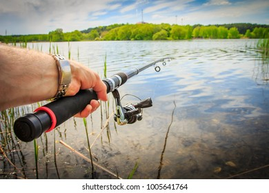 Fishing on lake. Fishing rod in fisherman's hand against lake in summer in nature on bright sunny day. To fish on river by spinning. fisherman is holding fishing rod close-up