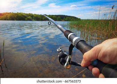Fishing on the lake on a sunny day. Hands and fishing rod of the fisherman macro. Fishing rod and hands of the fisherman over the lake water