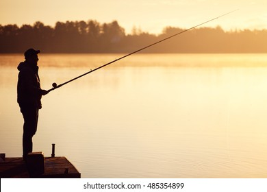 Fishing on morning autumn lake in sunrise