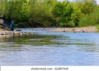 Fishing on the mountain river. Trout fishing. Fisherman fishing in the mountains