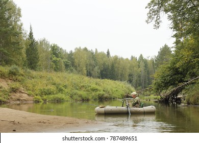 Fishing on the river. A fisherman on a rubber boat.