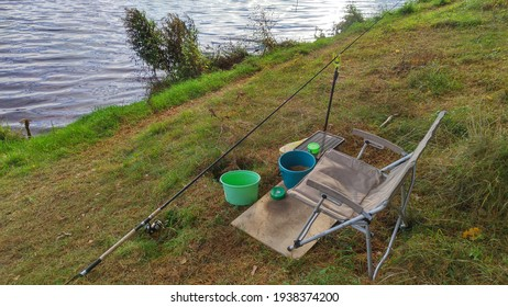 Fishing on the river, folding chair, feeder rod with reel, bucket with bait for fish and jars with live bait