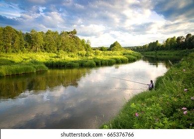 Fishing on the river in a rural place in the summer. Evening. A man with a fishing rod sitting on the river Bank. White clouds on blue sky. A beautiful rural landscape. Wildlife.