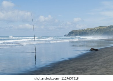 Fishing on a sandy beach near Raglan, Waikato, New Zealand.