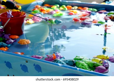 fishing in the paddling pool. Children's toys in the pool. Toy fish fishing rod. Cheerful children fishing, fishing in the paddling pool
