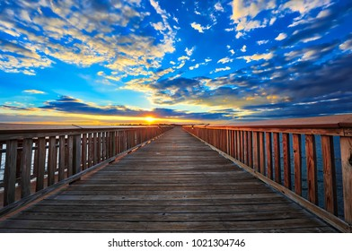 Fishing pier on the Chesapeake bay in Maryland with the sun setting on the horizon