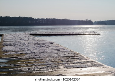 Fishing pier on a frozen lake. Bridge for mooring fishing boats and ice on the lake. Season winter.