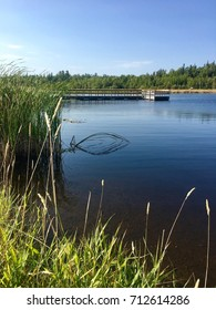 Fishing Pier on Rainy Lake on a Sunny Summer Day - Bright Blue Sky With Reflections