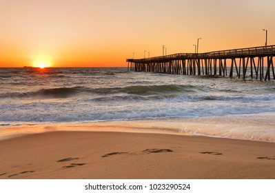 Fishing Pier at Sunrise at Virginia Beach, Virginia, USA. Virginia Beach, a coastal city in southeastern Virginia, lies where the Chesapeake Bay meets the Atlantic Ocean.