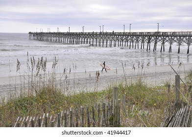 The fishing pier at Surf City, NC on Topsail Island just before dusk.  A surfer is carrying a surf board in the distance.
