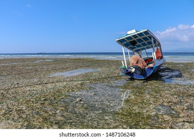 Fishing and pleasure boats on sand at low tide. Fishing boat at ebb tide in Gili Meno, Indonesia. Traditional wooden boat beached at sea coral. Traditional boat stranded in cause of low tide.