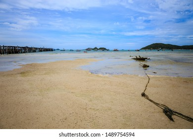 Fishing and pleasure boats on sand at low tide. Fishing boat at ebb tide in Chonbiri thailand. Traditional wooden boat beached at sea coral. Traditional boat stranded in cause of low tide