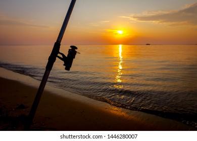 Fishing pole on the sandy beach, early dawn, sunrise, morning over Mediterranean sea.