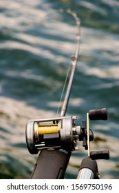 Fishing pole and reel with rod bent to the left with water diffused in bacground