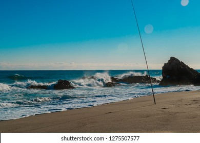 Fishing pole stuck in sand in front of waves crashing violently into boulders on sunny winter morning.
