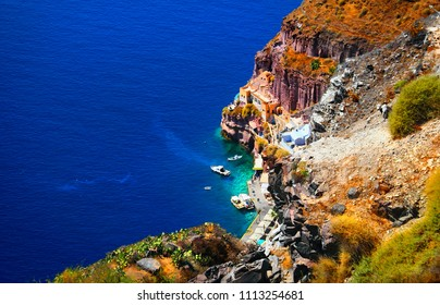 Fishing port in Thera (Thira, Fira) Santorini island, Cyclades, Southern Greece. Beautiful scenery, black volcanic rocks, traditional cycladic houses, pier, harbour, boats and blue water of Aegean Sea