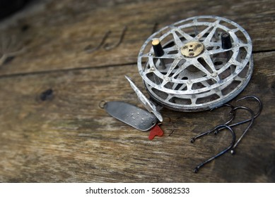 Fishing reel fishing line and hooks on a dark wooden background