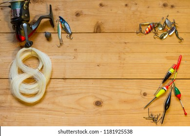 Fishing reel, a fishing line, a fishing lure and fishhooks, a bobber on the wooden table.