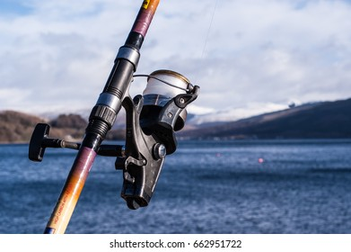 Fishing reel with sea, sky and mountain in the background
