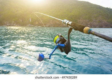 Fishing reel and sunrise at island