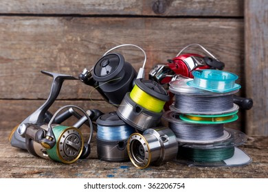 fishing reels and spoole with line on background of wooden timbers