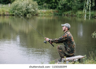 Fishing in river.A fisherman with a fishing rod on the river bank. Man fisherman catches a fish pike.Fishing, spinning reel, fish, Breg rivers. - The concept of a rural getaway. Article about fishing.