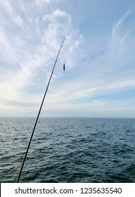 Fishing rod with bait in front of a beautiful seaview with light white clouds against blue sky in the horizon.