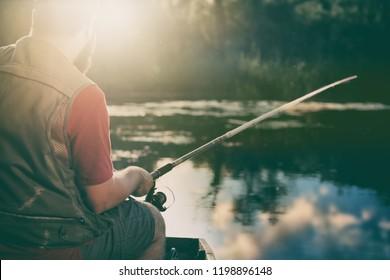 Fishing rod close-up, man fishing with a beautiful sunrise front him