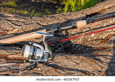 Fishing rod with fishing reel on the natural background. Spinning on the old tree with brown bark.