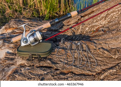 Fishing rod with fishing reel on the natural background. Fish stringer and box for baits. Spinning and other objects on the old tree with brown bark.