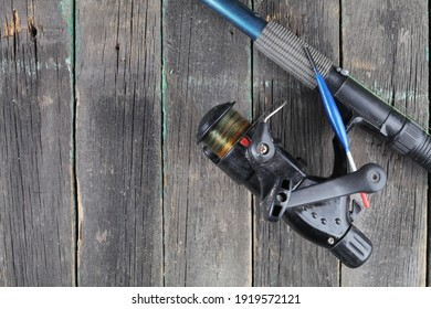 Fishing rod with reel on a wooden background, copy space.