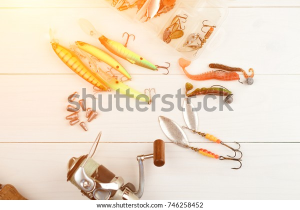 Fishing rod with reel, spoon baits, tackles and wobblers in box for catching or fishing a predatory fish on white vintage wooden background.