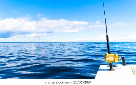 Fishing rod in a saltwater private motor boat during fishery day in blue ocean. Successful fishing concept