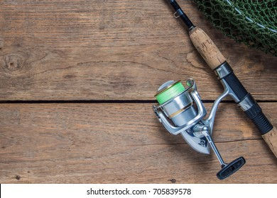 Fishing rod and spinning reel with line on wooden background with free space, Top view.