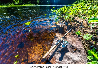 Fishing rod at summer river water. Fishing rod view